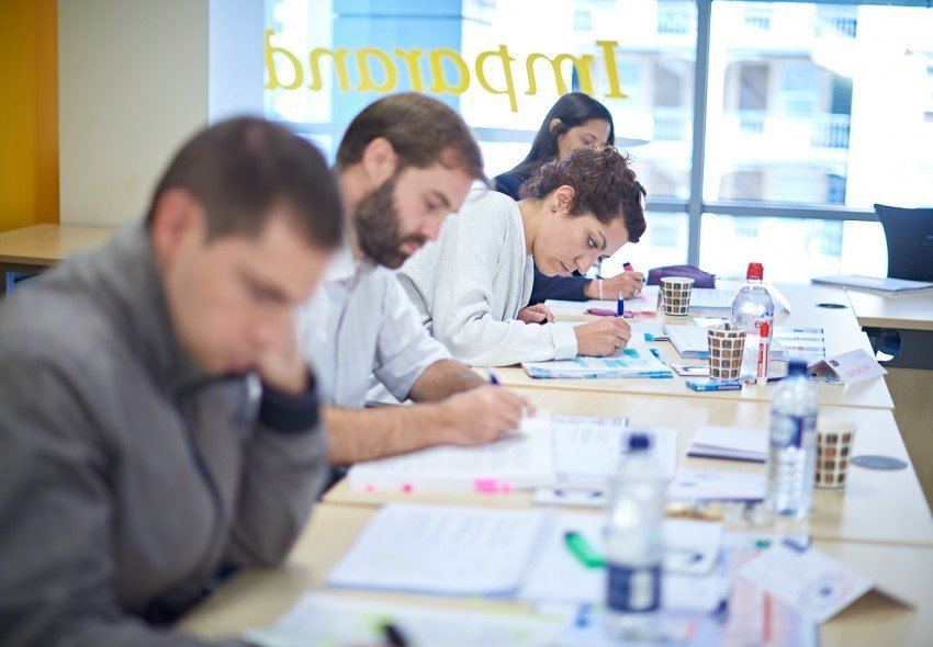 Project management course delegates with their heads down, taking notes